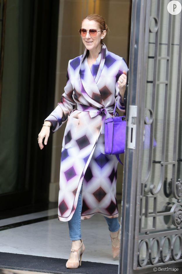 Céline Dion porte un manteau long imprimé et un sac Fendi.