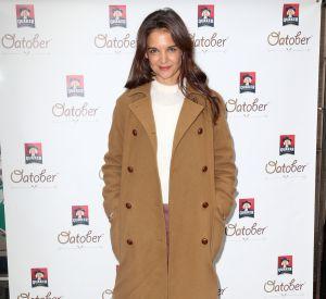Katie Holmes en manteau beige, pull en cachemire, jupe courte en cuir couleur bordeaux et chaussures à talons noires.