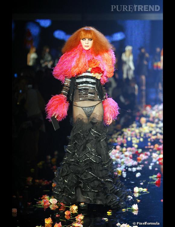 (Intro sous le diaporama...) En descendant le long de la silhouette, on reconnaît tous les codes qui font l'attitude Rykiel : l'évanescence de l'autruche, le confort du gilet, les rayures, les strass, les chaussures à compensé, le bouquet de roses, les tons de rouge mariés au noir, la sexualité et le plaisir féminin revendiqués. Comme libéré par cette femme affranchie, Christian Lacroix ose la robe la plus sexy qu'il a jamais imaginée. L'organza voile a peine la zone de la taille et des hanches, parée sous ce voile d'un triangle de tissu noir strassé. Oui, c'est le pubis qui est le centre mis en lumière dans cette silhouette et c'est l'hommage à Sonia Rykiel qui l'autorise à Christian Lacroix ! Ajoutons également combien la signature Lacroix est omniprésente : dans les deux tons utilisés dans le col et les manchettes en autruche, le rose shocking se marie à l'orange quasi vermillon chez ce magicien de l'alliance des couleurs.