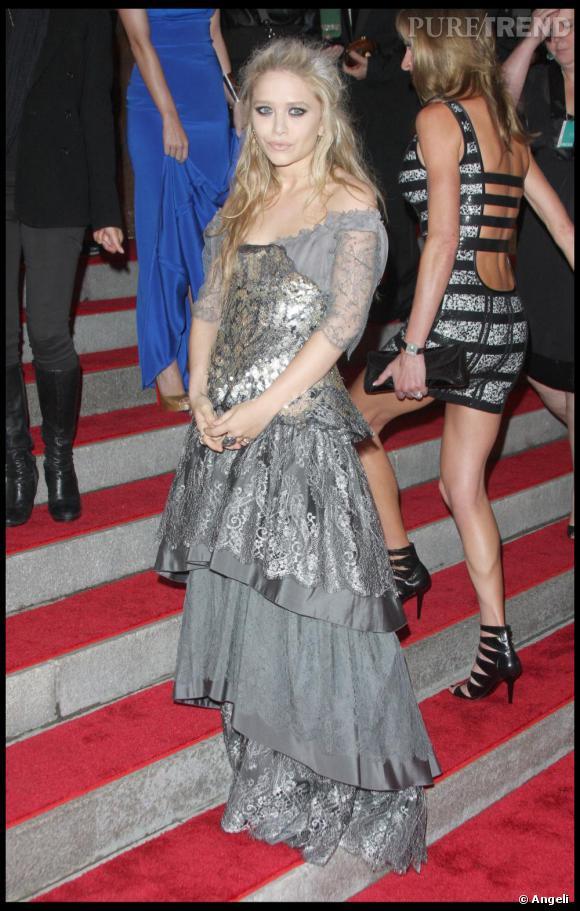Deux effets complètement opposés de gris entre Mary Kate Olsen qui porte une robe d'un gris mousseux et romantique et la jeune femme que l'on voit, de profil, montant l'escalier, portant une tenue grise, lisse et graphique. Le gris peut jouer tantôt l'harmonie ou tantôt le caractère. Tout va dépendre, de la nuance, de la matière et de la forme.Pour Mary Kate Olsen, tout se joue dans l'harmonie. La nuance claire apporte douceur et légèreté. L'aspect argenté du tissu met en valeur ses yeux bleus et les reflets cendrés de ses cheveux. Le volume de la robe reprend le volume de ses cheveux comme dans les meilleurs contes de fées.