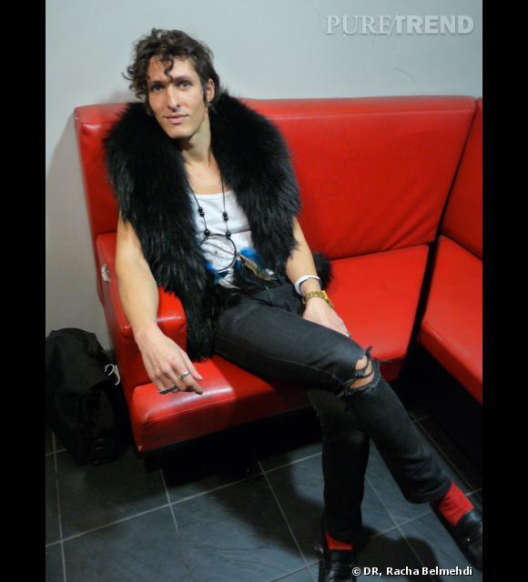 Bruno, chanteur stylé sur canapé rouge. Notez au niveau des chaussettes le rappel de couleur qui signe l'homme élégant.