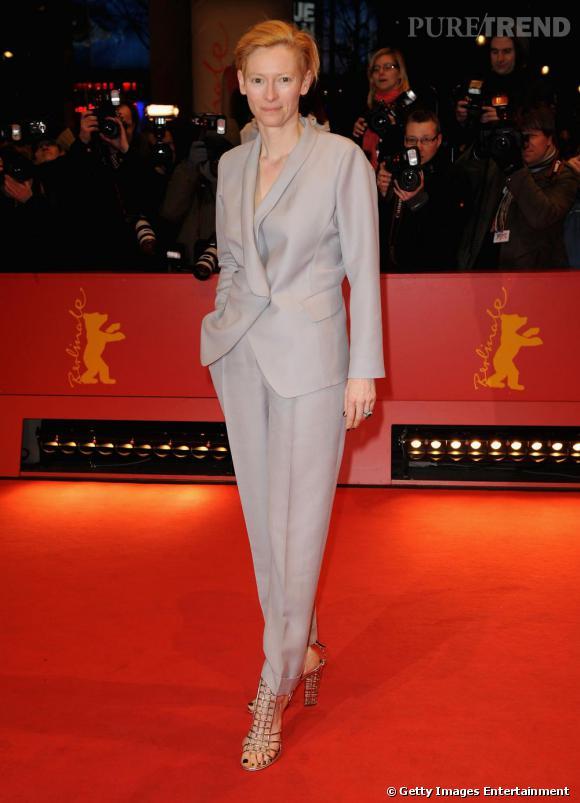 Tilda ose le total look gris clair, veste ample sur carrot pant. Un ensemble difficle à assumer mais que l'actrice apprivoise à merveille. Bien joué pour les sandales or, essentielles ici pour féminiser sa tenue.