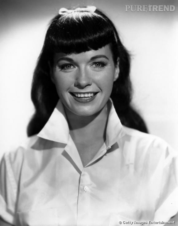 """Mannequin vedette des années 50, Bettie Page fait partie des premières pin-up à avoir posé pour Playboy. Côté look, elle cultive une allure ultra rétro, très mode pour l'époque, la frange coupée court, asymétrique et légèrement gonflée. Le noeud dans les cheveux ajoute une touche girly très """"Grease""""."""