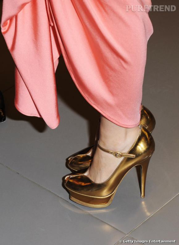 Kylie tente des escarpins à plateaux or : très audacieux avec une robe corail aussi flashy et sexy