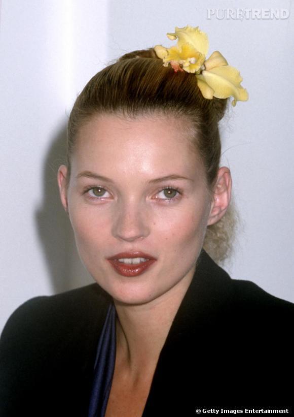 1996 : La Brindille joue les naïades, une fleur posée sur un chignon de danseuse. Le visage ainsi dégagé, elle affiche un teint zéro défaut sublimé par une bouche grenat.