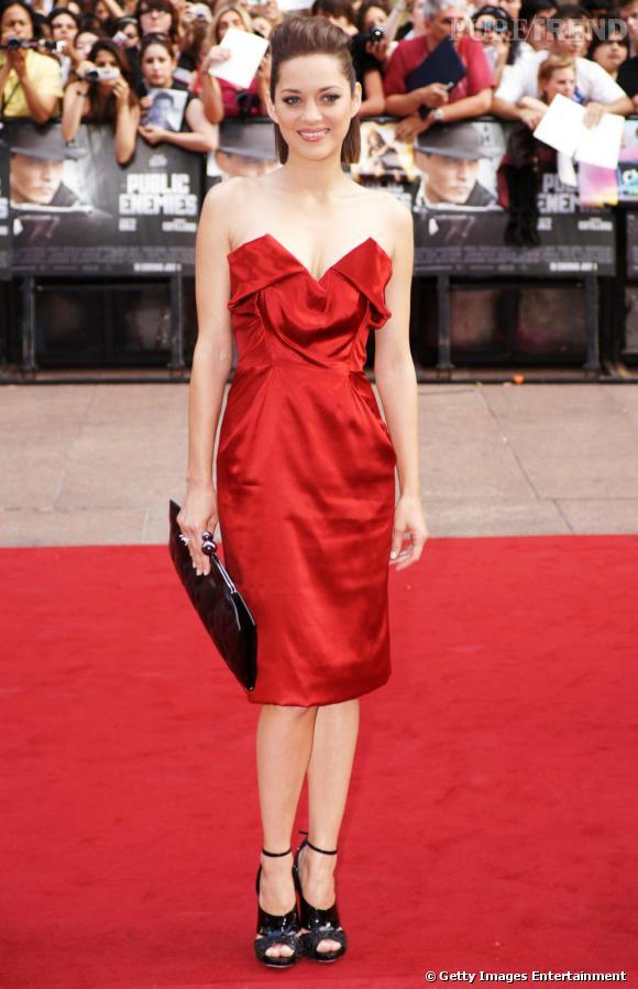 Avec une robe Vivienne Westwood d'un rouge sensuel au décolleté audacieux, Marion joue le glamour subtil.