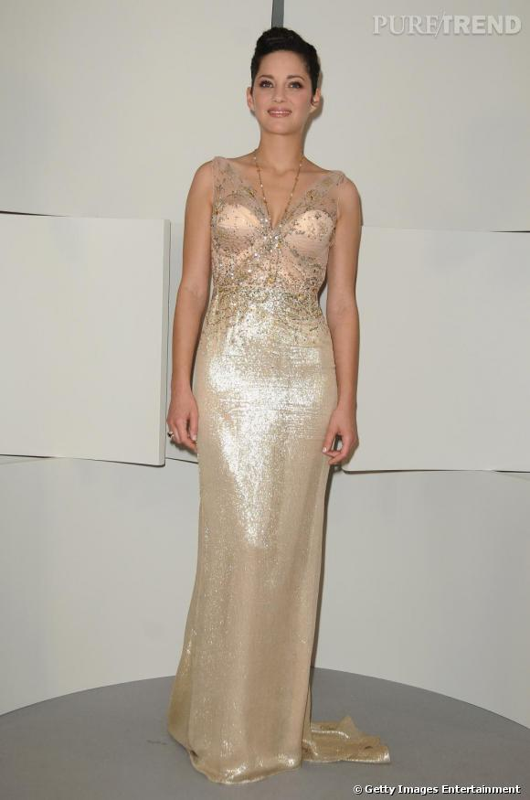 Marion profite d'une robe Dior moulante pour sublimer sa silhouette. Ornée de bretelles en dentelle, elle laisse entrevoir un bustier très lingerie sans une once de vulgarité.
