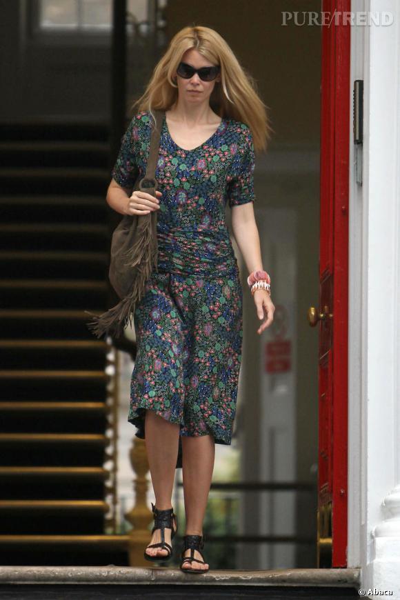 Robe à fleurs plus ajustée aux hanches grâce à un jeu de drapés, sac à franges et sandales plates, Claudia Schiffer reste printanière en ce début de septembre.