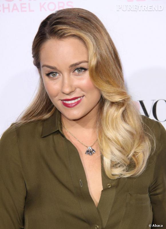 Les cheveux tombant en cascade de boucles, la blonde opte pour une mise en beauté rétro.