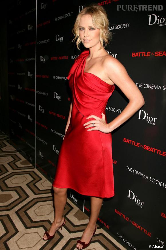 Subtile séductrice en rouge piquant, Charlize Theron dédramatise la couleur de sa robe avec une coiffure bohème.