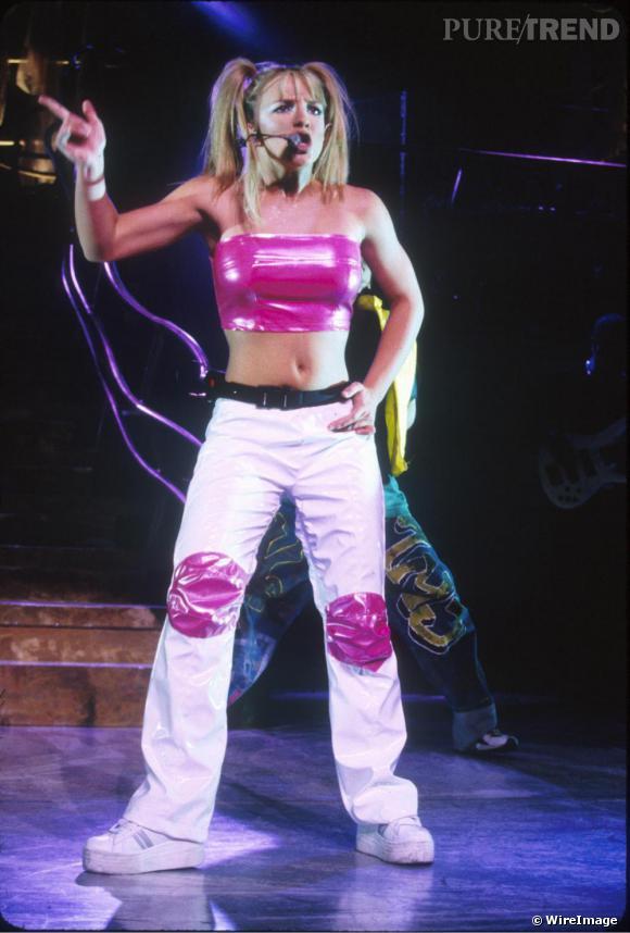 Pour sa première tournée, ...Baby One More Time Tour en 1999, Britney Spears apparaît en baggy flashy et en bustier latex, mais les couettes de petites filles sont toujours là.