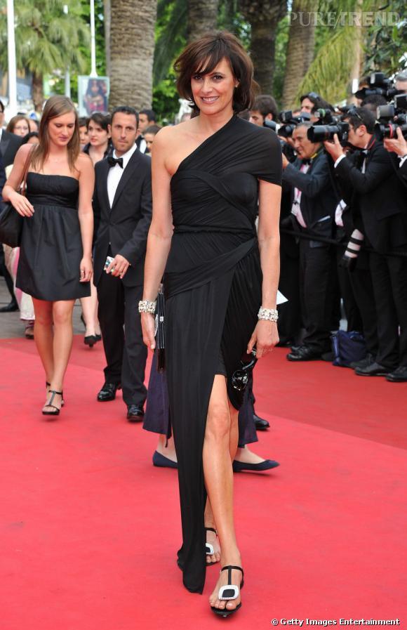 Cannes 2011 : Inès de la Fressange, à plat sur tapis rouge (des sandales Roger Vivier), tente une robe asymétrique toute en drapés Carven.