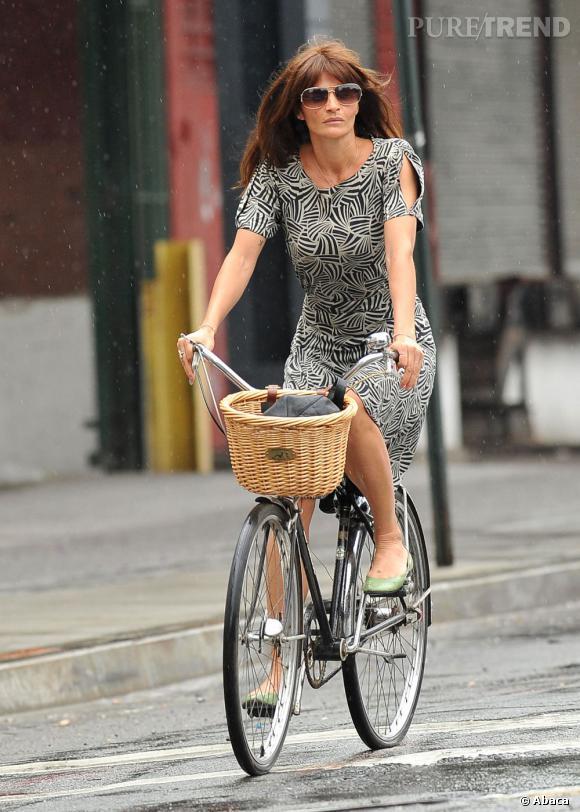 La maman tendance    :    Helena Christensen joue les mamans tendance à vélo. Ici dans une robe imprimée avec de simples ballerines aux pieds, elle est divine.