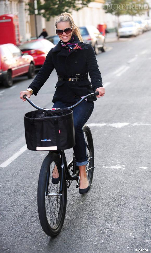 """Le Top Model    :  quand """"The Body"""" Elle Macpherson fait du vélo, elle n'en perd pas son sens du style. Caban noir cintré et jean slim, voici un look de citadine chic."""