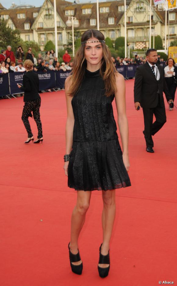 La jeune femme prouve son sens du style avec une petite robe noire en tissu brillant pimentée d'accessoires tendance.