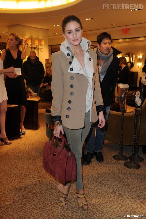 Jean kaki, manteau en peu beige, top loose blanc, Olivia Palermo pimente son look avec des sandales jungle Alexandre Birman et un sac en daim rouge.
