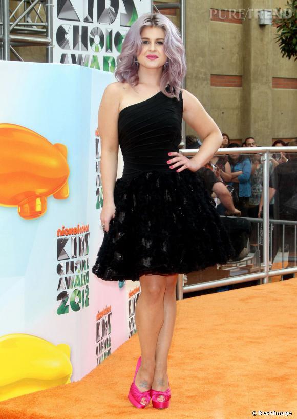 Elle apporte une jolie touche pop à la tenue avec une paire de peep-toe rose fluo Giuseppe Zanotti.