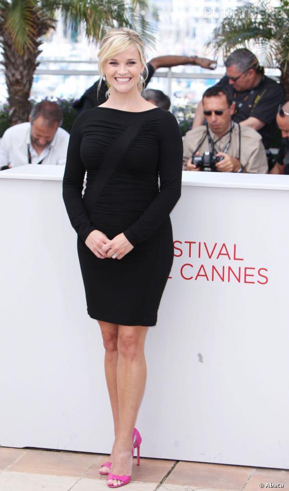 La jeune femme prend la pose dans une robe noire moulante Versace qui met en valeurs ses premières rondeurs. Elle prend de la hauteur sur une paire d'escarpins Manolo Blahnik qui apporte en plus une touche de couleur au look.