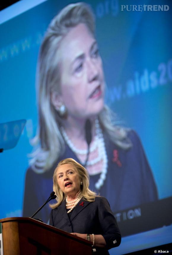 Hillary Clinton, très élégante avec les cheveux mi-longs et un tailleur chic, n'oublie pas le ruban rouge, symbole de la lutte contre le sida