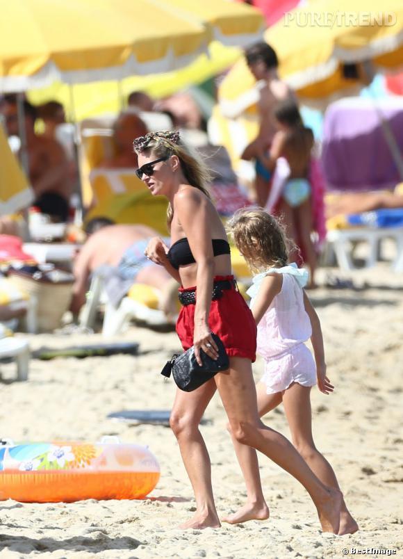 Sur le sable chaud, elle tombe le haut pour dévoiler un bikini bandeau.