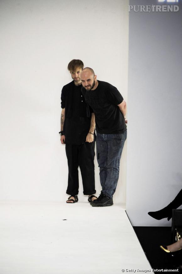 """Nom : Edward Meadham et Benjamin Kirchhoff, alias """"Meadham Kirchhoff"""".        CV :  Duo franco-anglais, Edward Meadham et Benjamin Kirchhoff sortent diplômés de la Saint Martin School en 2002. Après avoir lancé leur label de prêt-à-porter homme sous le nom de """"Benjamin Kirchhoff """", les deux jeunes gens font défiler Meadham Kirchhoff pour la femme en 2006. Régulièrement nommés dans la catégorie espoirs et talents émergents au British Fashion Awards, les créateurs remportent le titre en 2010. Leurs défilés sont parmi les plus courus de la Fashion Week de Londres en raison d'une particulière bonne humeur. Leur marque est distribuée chez Net-à-Porter, Harvey Nichols et Browns à Londres, Maxfield à LA, Joyce à Hong Kong Ikram à Chicago, 10 Corso Como à Séoul and RA en Belgique.       Signature :  Avec une bonne dose d'humour, de sens de la mise en scène et une passion pour le """"ridicool"""", Meadham Kirchhoff est devenu au fil des saisons l'exemple type du label funky trash dont Londres est friand. Une liberté totale qui trouve sa forme la mieux incarnée dans les silhouettes colorées et volontairement too-much du duo, qui redéfinissent l'adulescente pop. Débarrassés de toutes inhibitions, les créateurs osent le mélange des genres et font bien."""