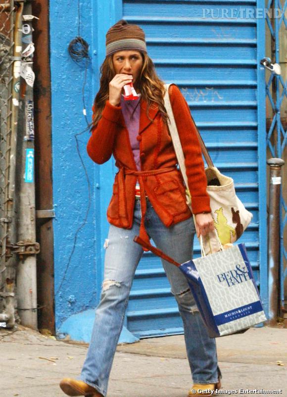 Jennifer Aniston grignotte une barre de chocolat en pleine rue.