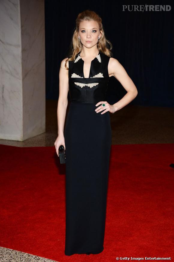 Natalie Dormer en robe longue noire et plastron graphique.