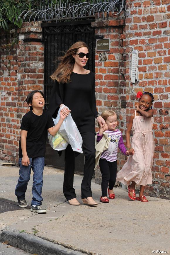Angelina Jolie avec Shiloh sa fille biologique, Pax à sa droite et Zahara à sa gauche qu'ils ont adopté avec Brad Pitt.