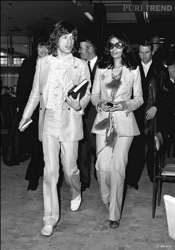 Costume clair en tissu brillant porté sur une chemise à jabots et chaussures blanches, Mick Jagger fait sensation en 1971.