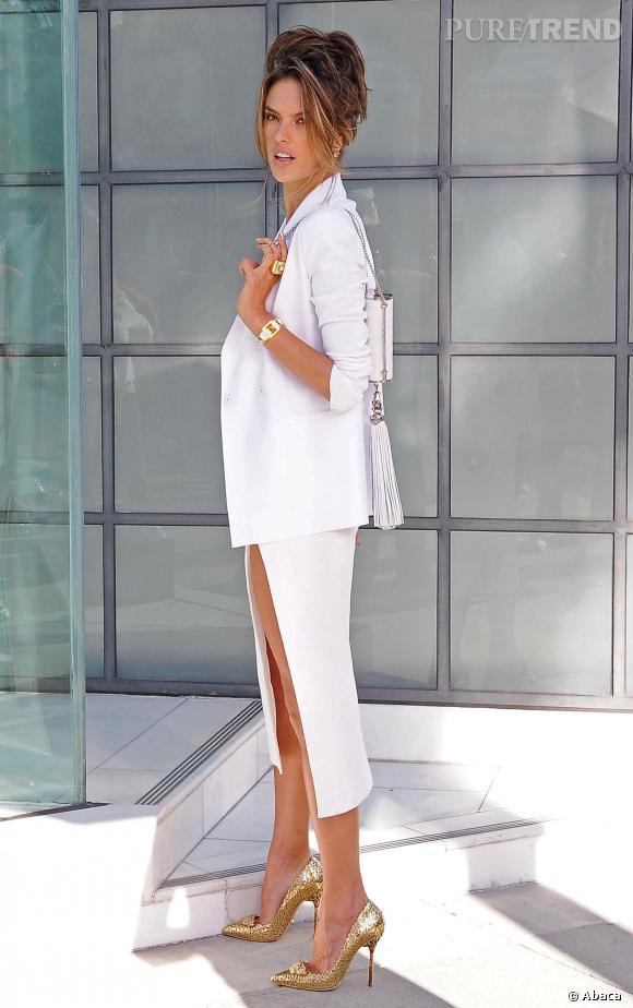 Alessandra Ambrosio pose dans un ensemble Chanel composée d'une jupe fendue et d'un blazer long immaculé.