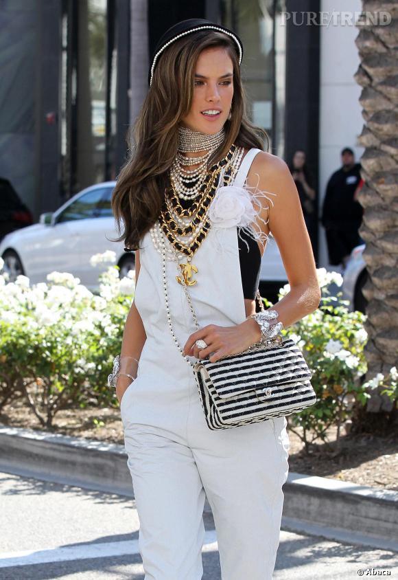 Alessandra Ambrosio dans une salopette blanche et accumulation de bijoux Chanel.