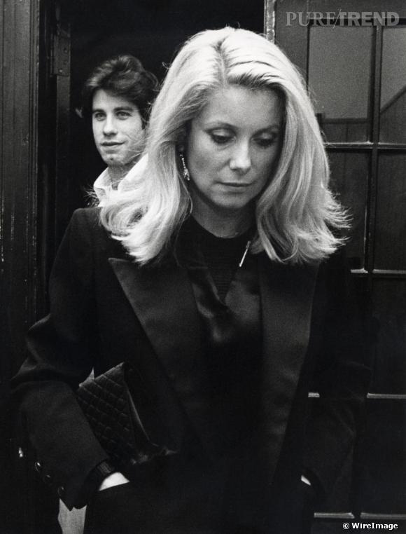 Pour entrer dans les années 80, Catherine Deneuve affiche un carré mi-long porté avec une raie sur le côté. Côté look ? Le trench est de sortie !