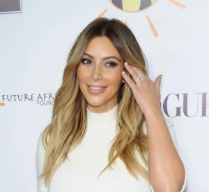 Kim Kardashian et Kanye West entourés de paparazzi.
