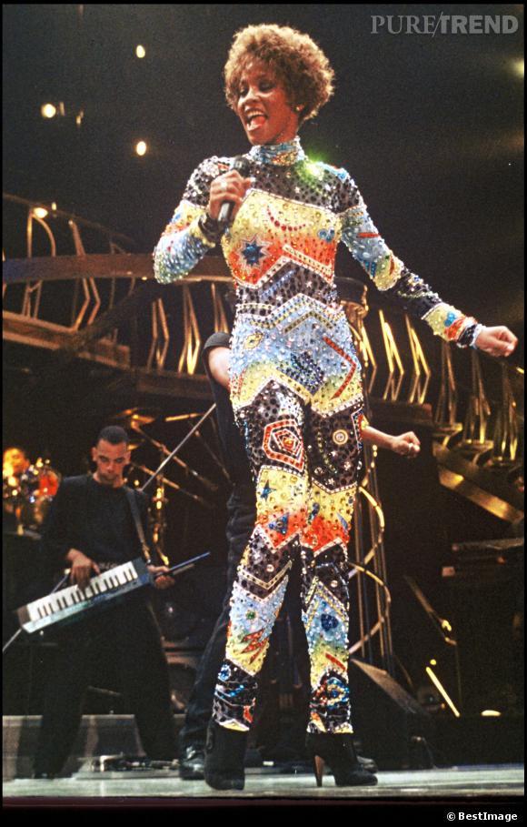 """En concert, Whitney Houston porte une combinaison brodée de strass et de perles. Et comme, ce n'est """"pas assez"""", de multiples couleurs viennent s'ajouter à cela..."""