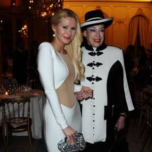 Tatiana Delarue mise sur une robe moulante, tandis que Geneviève de Fontenay dévoile son traditionnel chapeau noir à bandes blanches.