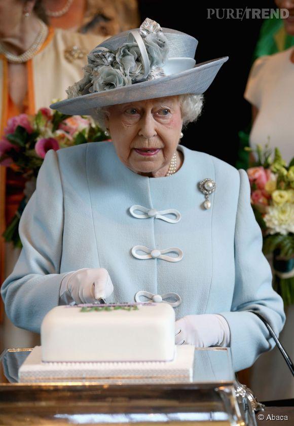 Elisabeth II, bien vivante, coupe un gâteau lors du 100ème meeting du Women Institute.