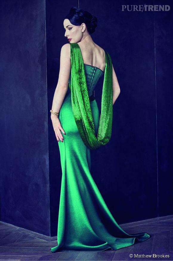 Dita Von Teese, vêtue d'une robe fourreau corsetée en satin vert émeraude, au dos drapé en écharpe.