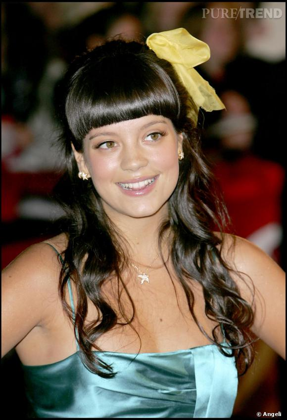 Il n'aura pas fallu attendre longtemps pour que Lily Allen commande une frange. A cette époque, elle la préfère un brin bombée. Cheveux ondulés et noeud jaune dans les cheveux, l'icône pop fait son entrée.