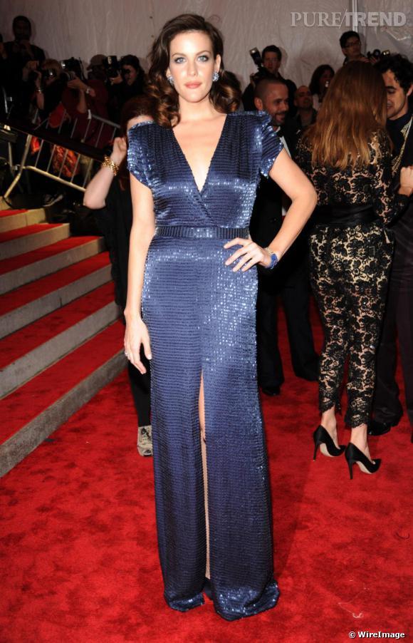 Liv Tyler parie sur une ouverture sur le devant de sa robe. Plus discrète, elle permet à l'actrice de mettre en avant sa robe à sequins, pièce déjà imposante.