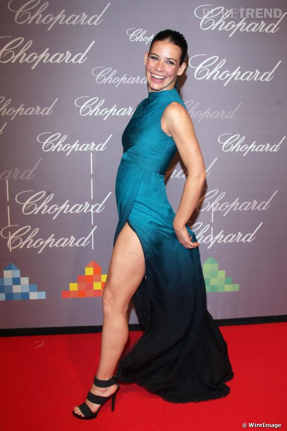 L'actrice de la série  Lost , Evangeline Lilly, opte pour un robe fermée qu'elle glamourise à l'aide d'un fendu XXL. Elle semble à l'aise et fière de dévoiler ses jambes galbées par des années de sport.