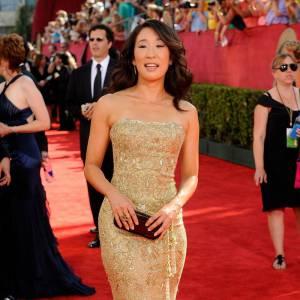 Si Sandra Oh n'est pas réputée pour être l'une des stars les plus féminines, quand il s'agit de fouler le red carpet des Emmy Awards elle sort le grand jeu et joue la carte du glamour. Pour cela, rien de mieux qu'une robe fourreau dorée qui souligne sa silhouette et illumine son teint.