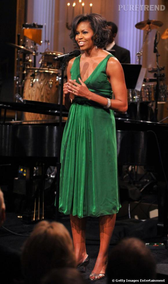Michelle Obama aime les pièces colorées. Et elle a bien raison. Notamment lorsqu'elle opte pour une robe verte décolletée. De cette façon, elle flatte sa ligne et son buste féminin.