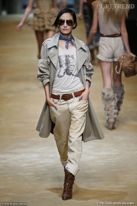 Défilé D&G Printemps-Eté 2010    Un look plus masculin pour le trench du défilé D&G. Il retrouve ses origines associé à un jean boyfriend et un t-shirt imprimé. Manches retroussées et grand ouvert, voilà une silhouette de détective chic.