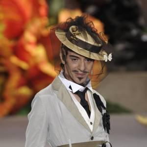 En 2010, John Galliano pratique l'art de la mise en scène aussi bien pour ses défilés que pour ses propres apparitions. Le créateur a fait de l'extravagance sa ligne de conduite.