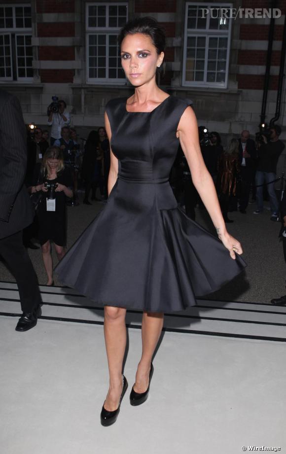 Victoria Beckham opte pour une robe noire très Mad Men, les cheveux attachés et escarpins noirs classiques.