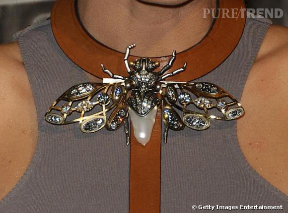 Un papillon précieux se pose à l'encolure.