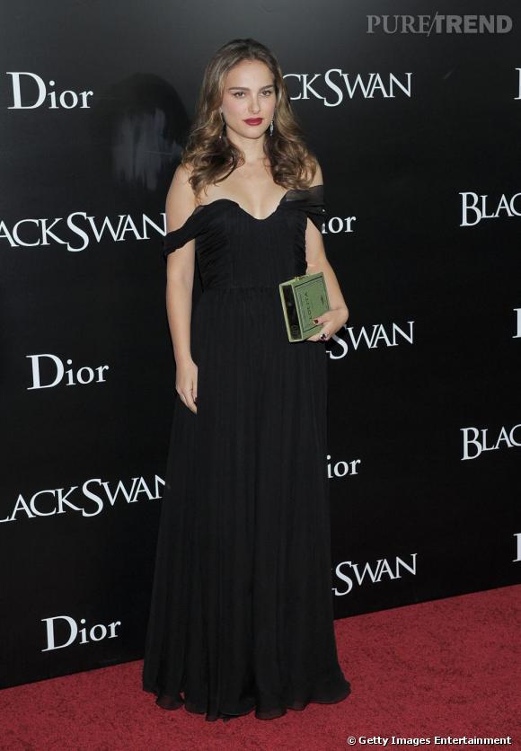 """Natalie Portman subjugue dans une robe en mousseline Christian Dior, armée d'une pochette Olympia Le-Tan devinée derrière le livre """"Lolita"""" de Vladimir Nabokov."""