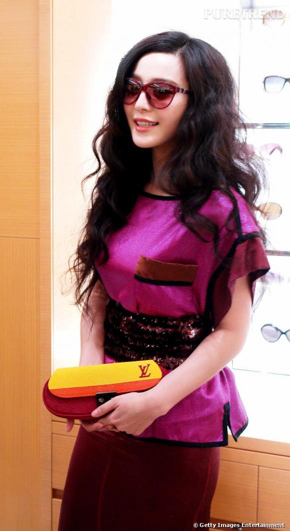 Fan Bing Bing mise sur un total look avec un top rose dont les détails fuchsia s'harmonise à la jupe. En guise de pochette, un modèle de la même collection flashy.