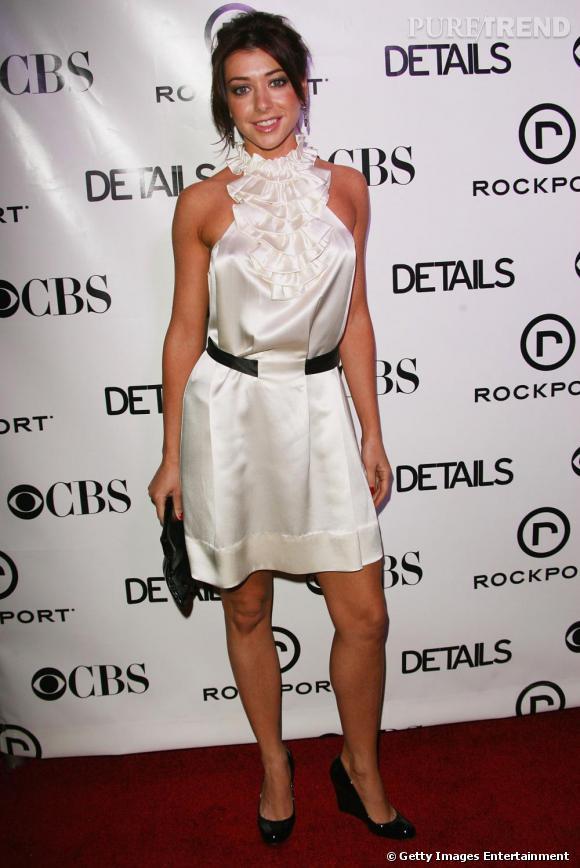 La jolie brunette est ravissante en petite robe blanche à froufrous sur le haut.