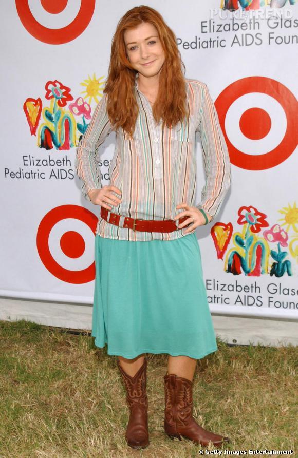 L'actrice joue les cow boy version girly avec une chemise crayonnée, une jupe (trop) longue et des santiags.